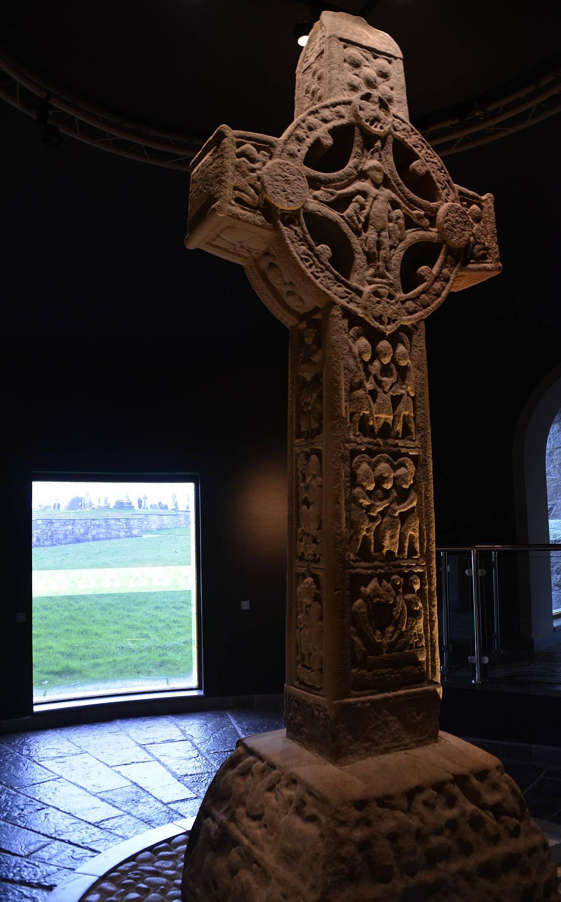 Alkuperäinen Cross of th e Scriptures ja taustalla näkyy ikkunasta raunioalue.