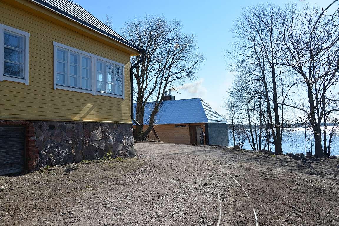 Lonnan saarella on seitsemän rakennusta, joista uusin taustalla tupruttava sauna.