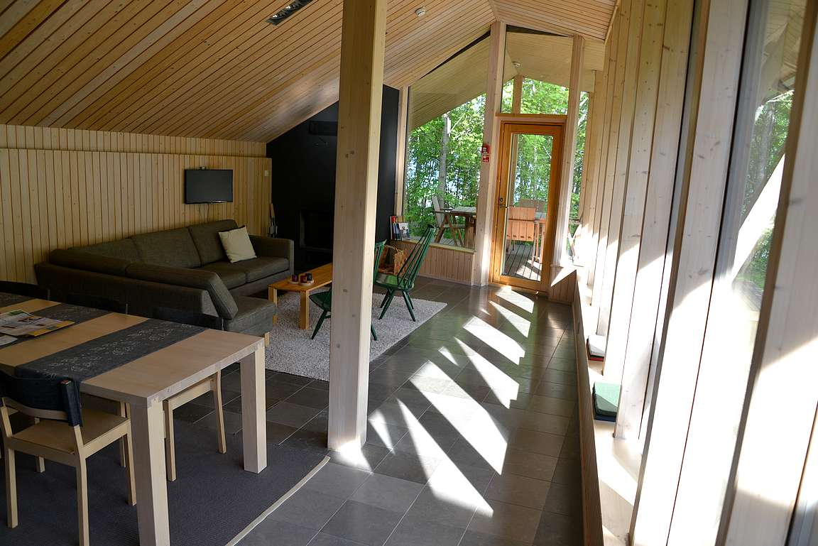 Olohuone ja taustalla terassilla näkyvä yksi ruokailuryhmä ulkosalla.