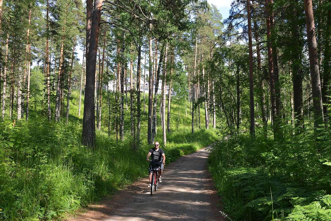 Polkupyöräily ja taustalla näkyvä hotelli Punkaharju kuuluu Punkaharjun pakollisiin ohjelmanumeroihin.