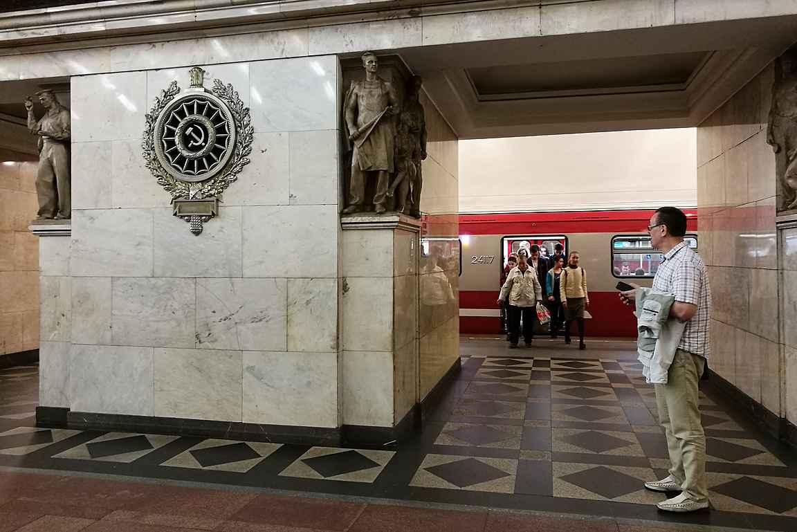 Narvskayan aseman työläisfigureeja ja taustalla harvinainen punaisen värinen metrojuna.
