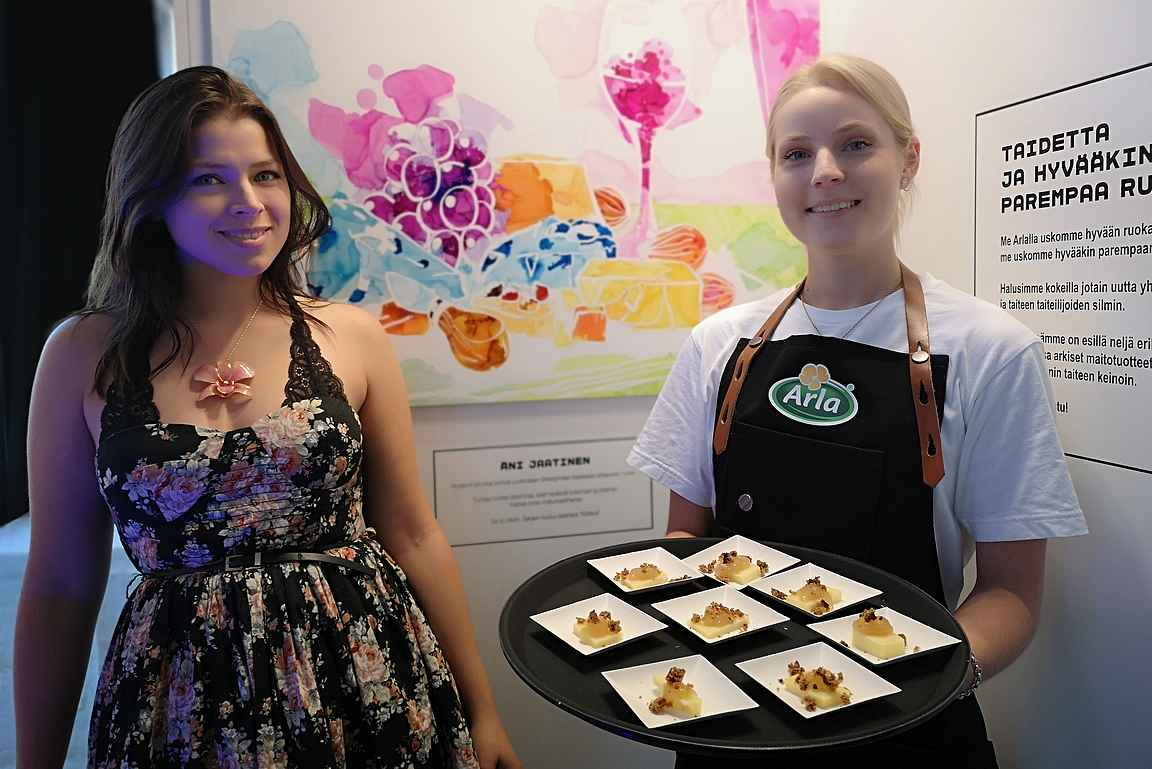 Taiteilija Äni Jaatinen teoksensa edessä, missä tarjoiltiin pieniä juustopohjaisia maisteluannoksia.
