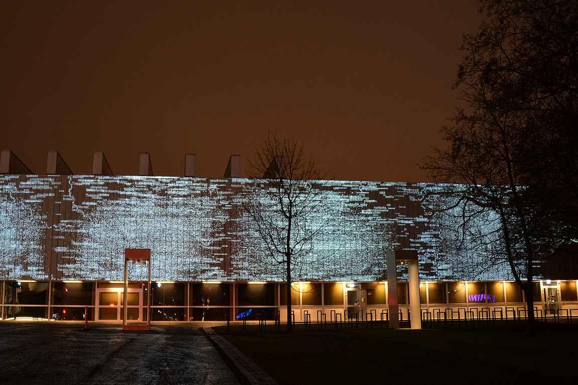 Tampereen yliopiston päärakennuksen seinään heijastetaan upea valoinstallaatio.