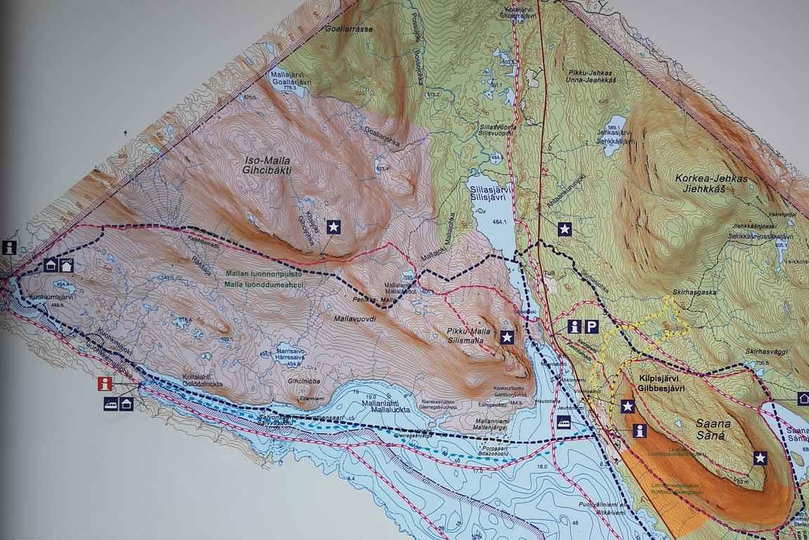 Karttakuvaa Kilpisjärven opastaulusta. Punainen katkoviiva on patikointireitti Mallan kansallispuistossa, sininen puolestaan hiihtoladut.